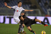 Francesco Totti (R) of AS Roma competes for the ball with Jose' Basanta of ACF Fiorentina during the TIM Cup match between AS Roma and ACF Fiorentina at Olimpico Stadium on February 3, 2015 in Rome, Italy.