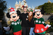 In this handout photo provided by Disneyland Resort , actress Madelaine Petsch and her boyfriend, TV and radio personality Travis Mills, share a special moment with Mickey Mouse and Minnie Mouse while celebrating the holidays at Disneyland Park December 13, 2019 in Anaheim, California.