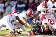 Marlon Humphrey #26, Ryan Anderson #22, Reuben Foster #10 and Geno Matias-Smith #24 of the Alabama Crimson Tide dive to recover a fumble by Ashton Shumpert #32 of the Mississippi State Bulldogs at Davis Wade Stadium on November 14, 2015 in Starkville, Mississippi.