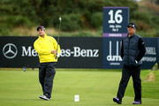 Mark Boucher plays off the 16th tee watched by Shane Warne during the second round of the 2014 Alfred Dunhill Links Championship at the Championship Links at Carnoustie on October 3, 2014 in Carnoustie, Scotland.