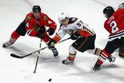 David Perron #57 of the Anaheim Ducks tries to control the puck between Niklas Hjalmarsson #4 and Duncan Keith of the Chicago Blackhawks move to the puck at the United Center on February 13, 2016 in Chicago, Illinois. The Ducks defeated the Blackhawks 3-2 in overtime.