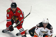 David Perron #57 of the Anaheim Ducks tries to control the puck between Niklas Hjalmarsson #4 and Andrew Shaw #65 of the Chicago Blackhawks move to the puck at the United Center on February 13, 2016 in Chicago, Illinois. The Ducks defeated the Blackhawks 3-2 in overtime.