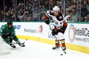 Hampus Lindholm #47 of the Anaheim Ducks skates the puck against Jamie Benn #14 of the Dallas Stars in the third period at American Airlines Center on October 13, 2018 in Dallas, Texas.