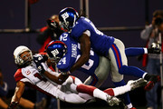 Larry Fitzgerald #11 of the Arizona Cardinals loses the ball in a tackle by Terrell Thomas #24 and C.C Brown #41 breaks away from Hakeem Nicks #88 of the New York Giants on October 25, 2009 at Giants Stadium in East Rutherford, New Jersey.