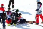 Keri Herman of the United States kneels next to James Woods of Great Britain after a fall by Woods during a Slopestyle official training session ahead of the the Sochi 2014 Winter Olympics at Rosa Khutor Extreme Park on February 7, 2014 in Sochi, Russia.