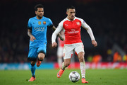 Alexis Sanchez of Arsenal is pursued by Dani Alves of Barcelona during the UEFA Champions League round of 16, first leg match between Arsenal FC and FC Barcelona at the Emirates Stadium on February 23, 2016 in London, United Kingdom.