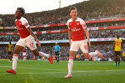 Mesut Ozil of Arsenal (r) celebrates scoring his sides second goal with Alex Iwobi during the Premier League match between Arsenal FC and Watford FC at Emirates Stadium on September 29, 2018 in London, United Kingdom.