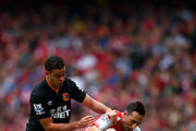 Santi Cazorla of Arsenal battles for the ball with Hatem Ben Arfa of Hull City during the Barclays Premier League match between Arsenal and Hull City at Emirates Stadium on October 18, 2014 in London, England.