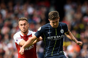 John Stones of Manchester City passes the ball under pressure from Aaron Ramsey of Arsenal during the Premier League match between Arsenal FC and Manchester City at Emirates Stadium on August 12, 2018 in London, United Kingdom.