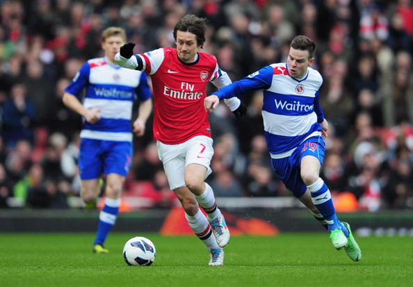 Tomas Rosicky of Arsenal holds off Danny Guthrie of Reading during the Barclays Premier League match between Arsenal and Reading at Emirates Stadium on March 30, 2013 in London, England.
