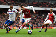 Mesut Ozil of Arsenal is challenged by Glen Johnson of Stoke City during the Premier League match between Arsenal and Stoke City at Emirates Stadium on April 1, 2018 in London, England.