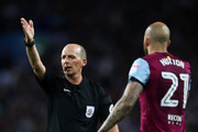 Referee Mike Dean in action as Alan Hutton of Aston Villa looks on  during the Sky Bet Championship Play Off Semi Final second leg match between Aston Villa and Middlesbrough at Villa Park on May 15, 2018 in Birmingham, England.