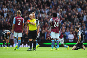 Referee Mike Dean turns away after showing the red card to Mike Williamson (R) of Newcastle United during the Barclays Premier League match between Aston Villa and Newcastle United at Villa Park on August 23, 2014 in Birmingham, England.