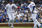 Kris Bryant (L) of the Chicago Cubs is greeted by Anthony Rizzo #44 of the Chicago Cubs bases after hitting a two-run homer against the Atlanta Braves during the third inning while wearing the #42 to commemorate Jackie Robinson Day on May 14, 2018 at Wrigley Field  in Chicago, Illinois.