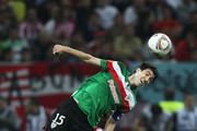 Andoni Iraola of Athletic Bilbao tangles with Arda Turan of Atletico Madrid  during the UEFA Europa League Final between Atletico Madrid and Athletic Bilbao at the National Arena on May 9, 2012 in Bucharest, Romania.