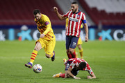 Yannick Carrasco of Atletico de Madrid tackles Lionel Messi of FC Barcelona during the La Liga Santander match between Atletico de Madrid and FC Barcelona at Estadio Wanda Metropolitano on November 21, 2020 in Madrid, Spain. Football Stadiums around Europe remain empty due to the Coronavirus Pandemic as Government social distancing laws prohibit fans inside venues resulting in fixtures being played behind closed doors.
