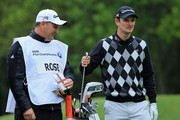Justin Rose of England looks on with caddie Mark Fulcher during the Pro-Am round prior to the BMW PGA Championship on the West Course at Wentworth on May 22, 2013 in Virginia Water, England.