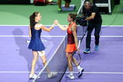 Agnieszka Radwanska of Poland shakes hands with Simona Halep of Romania after defeating her in a round robin match during the BNP Paribas WTA Finals at Singapore Sports Hub on October 29, 2015 in Singapore.