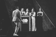 Image has been converted to black and white)  *** EDITORIAL USE ONLY IN RELATION TO THE BRIT AWARDS 2018 *** (L-R) Jesy Nelson, Perrie Edwards, Leigh Anne Pinnock and Jade Thirlwall of Little Mix present Stormzy with the Best British Male Solo Artist awardat The BRIT Awards 2018 held at The O2 Arena on February 21, 2018 in London, England.