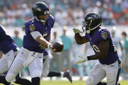 Quarterback Joe Flacco #5 of the Baltimore Ravens hands off to running back Justin Forsett #29 of the Baltimore Ravens  against the Miami Dolphins in the second quarter during a game at Sun Life Stadium on December 7, 2014 in Miami Gardens, Florida.
