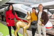 Rebecca Mir (L-R), Annemarie Carpendale and Nico Rosberg pose with a giant mockup of a Bambi trophy before they travel with the trophies to the Bambi Awards in Berlin by train at Munich Central Station on November 15, 2018 in Munich, Germany. The 70th Bambi Awards will take place on November 16, 2018 in Berlin.