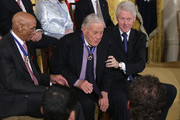 Former editor of the Washington Post Ben Bradlee (C) returns to his seat as baseball Hall-of-Famer Ernie Banks (L) and former U.S. President Bill Clinton (R) look on after Bradlee was presented with the Presidential Medal of Freedom in the East Room at the White House on November 20, 2013 in Washington, DC. The Presidential Medal of Freedom is the nation's highest civilian honor, presented to individuals who have made meritorious contributions to the security or national interests of the United States, to world peace, or to cultural or other significant public or private endeavors.