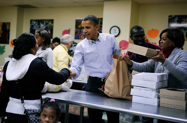 Barack Obama (AFP OUT) U.S. President Barack Obama (C) packs and delivers bags of food to area residents, with the help of his Mother-in-law Marian Robinson (R) ahead of the Thanksgiving Day holiday at Martha's Table on November 24, 2010, in Washington, DC.  The Obama family delivered turkeys and bags of food to needy families at Martha's Table, a 30-year-old non-profit that helps poor children, youth and families with food and clothing.