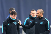 Lionel Messi of FC Barcelona talks with his teammate Dani Alves during a training session ahead of their UEFA Champions Leage round of 16 second leg match against Arsenal FC at Ciutat Esportiva on March 15, 2016 in Barcelona, Spain.