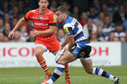 George Ford of Bath passes the ball watched by Ben Youngs during the Aviva Premiership match between Bath and Leicester Tigers at the Recreation Ground on September 20, 2014 in Bath, England.