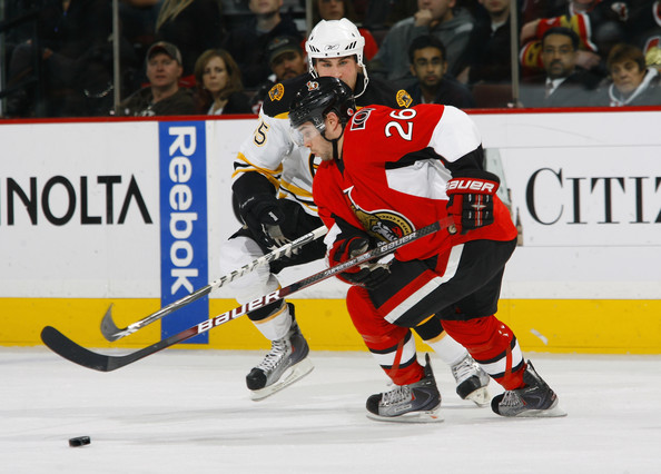 Ryan Shannon #26 of the Ottawa Senators dekes around Johnny Boychuck #55 of the Boston Bruins during a game at Scotiabank Place on December 21, 2009 in Ottawa, Canada.