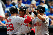 Daniel Nava #29 of the Boston Red Sox is congratulated by Mookie Betts #50, Xander Bogaerts #2, and Yoenis Cespedes #52 after hitting a grand slam home run during the 6th inning of the game against the Kansas City Royals at Kauffman Stadium on September 14, 2014 in Kansas City, Missouri.