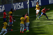 David Luiz of Brazil celebrates scoring his team's first goal past goalkeeper Claudio Bravo of Chile during the 2014 FIFA World Cup Brazil round of 16 match between Brazil and Chile at Estadio Mineirao on June 28, 2014 in Belo Horizonte, Brazil.