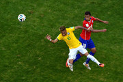 Neymar of Brazil and Gonzalo Jara of Chile compete for the ball during the 2014 FIFA World Cup Brazil round of 16 match between Brazil and Chile at Estadio Mineirao on June 28, 2014 in Belo Horizonte, Brazil.