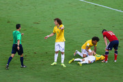 Neymar of Brazil lies on the field after a challenge as teammate David Luiz appeals to referee Carlos Velasco Caballo and James Rodriguez of Colombia looks on during the 2014 FIFA World Cup Brazil Quarter Final match between Brazil and Colombia at Castelao on July 4, 2014 in Fortaleza, Brazil.