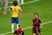 Thomas Mueller celebrates scoring his team's first goal with Mesut Oezil of Germany during the 2014 FIFA World Cup Brazil Semi Final match between Brazil and Germany at Estadio Mineirao on July 8, 2014 in Belo Horizonte, Brazil.