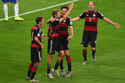 Thomas Mueller of Germany celebrates scoring his team's first goal with Mats Hummels, Mesut Oezil (L) and Benedikt Hoewedes (R) during the 2014 FIFA World Cup Brazil Semi Final match between Brazil and Germany at Estadio Mineirao on July 8, 2014 in Belo Horizonte, Brazil.