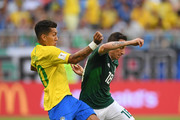 Roberto Firmino of Brazil tackles Andres Guardado of Mexico during the 2018 FIFA World Cup Russia Round of 16 match between Brazil and Mexico at Samara Arena on July 2, 2018 in Samara, Russia.