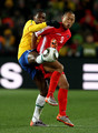 Juan of Brazil and Jong Tae-Se of North Korea battle for the ball during the 2010 FIFA World Cup South Africa Group G match between Brazil and North Korea at Ellis Park Stadium on June 15, 2010 in Johannesburg, South Africa.