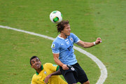 Luiz Gustavo of Brazil competes with Diego Forlan of Uruguay during the FIFA Confederations Cup Brazil 2013 Semi Final match between Brazil and Uruguay at Governador Magalhaes Pinto Estadio Mineirao on June 26, 2013 in Belo Horizonte, Brazil.