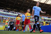 Diego Forlan of Uruguay walks out with a mascot and his team-mates prior to the FIFA Confederations Cup Brazil 2013 Semi Final match between Brazil and Uruguay at Governador Magalhaes Pinto Estadio Mineirao on June 26, 2013 in Belo Horizonte, Brazil.