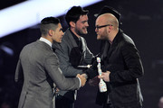 Jonny Buckland and Will Champion of Coldplay receive the award for British Live Act from Louis Smith and Jack Whitehall on stage during the Brit Awards 2013 at the 02 Arena on February 20, 2013 in London, England.