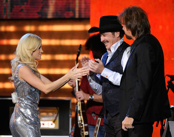Carrie Underwood (L-R) Singer Carrie Underwood with musicians Kix Brooks and Ronnie Dunn of the band Brooks & Dunn speak onstage during Brooks & Dunn's The Last Rodeo Show at MGM Grand Garden Arena on April 19, 2010 in Las Vegas, Nevada.