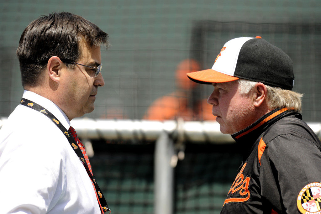 Executive Vice President of Baseball Operation John Duquette of the Baltimore Orioles, and Buck Showalter #26 of the Baltimore Orioles, talk before a baseball game against the Boston Red Sox on June 15, 2013 at Oriole Park at Camden Yards in Baltimore, Maryland.