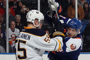 Rasmus Ristolainen #55 of the Buffalo Sabres hits Kyle Okposo #21 of the New York Islanders during the first period at the Nassau Veterans Memorial Coliseum on April 4, 2015 in Uniondale, New York.