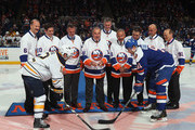 Former New York Islanders captain Ed Westfall prepares to drop the puck between Brian Gionta #12 of the Buffalo Sabres and John Tavares #91 of the New York Islanders at the Nassau Veterans Memorial Coliseum on April 4, 2015 in Uniondale, New York.