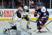 Playing in his first NHL game, Andrey Makarov #1 of the Buffalo Sabres makes the save as Josh Bailey #12 of the New York Islanders looks for a rebound of the New York Islanders at the Nassau Veterans Memorial Coliseum on April 4, 2015 in Uniondale, New York.