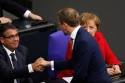 German Chancellor Angela Merkel (R) looks on as Christian Lindner (C), leader of the free democratic FDP party, greets German Vice Chancellor and Foreign Minister Sigmar Gabriel at the beginning of a session at the Bundestag (lower house of parliament) on November 21, 2017 in Berlin. / AFP PHOTO / Odd ANDERSEN
