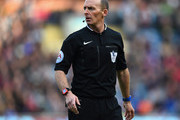 Referee Mike Dean looks on during the Barclays Premier League match between Burnley and Arsenal at Turf Moor on April 11, 2015 in Burnley, England.