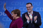 German Chancellor and Chairwoman of the German Christian Democrats (CDU) Angle Merkel waves to delegates as her colleague Jens Spahn, who has been an outspoken critic of Merkel and is slated to become the next German health minister, looks on after Merkel spoke to delegates at the 30th CDU party congress on February 26, 2018 in Berlin, Germany. The CDU is meeting to confirm the party's coalition contract with the German Social Democrats (SPD) and to elect a new general secretary. The CDU is currently set to go into a government coalition with the SPD in coming weeks. The congress comes the day after Merkel announced her choice of CDU government cabinet members that includes an outspoken critic of Merkel, Jens Spahn.