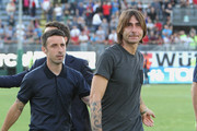 Daniele Conti  and Andrea Cossu of Cagliari  greets fans at the end of his career  during the Serie A match between Cagliari Calcio and Udinese Calcio at Stadio Sant'Elia on May 31, 2015 in Cagliari, Italy.